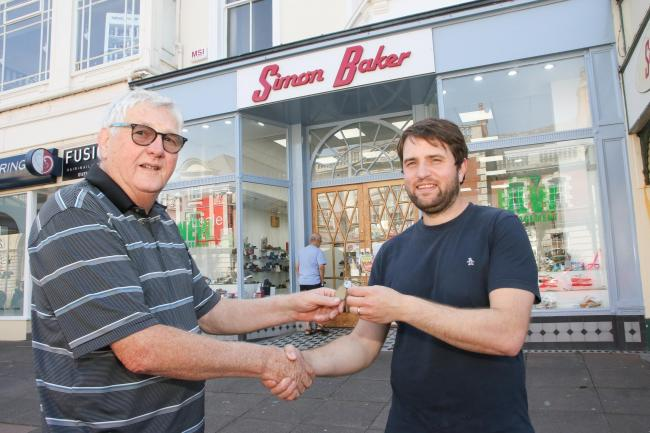 New owner Hal Holmes-Pierce receives the keys from previous owner Jeff Duckenfield who owned the shop since 1971. KR040719b