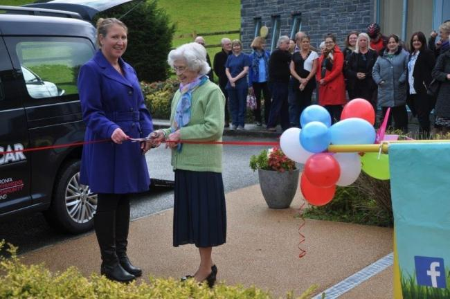 Mrs Margaret Griffiths, aged 92, one of those who will benefit from the community transport scheme, cuts the ribbon to officially launch the initiative, along with volunteer co-ordinator Maria Jones.