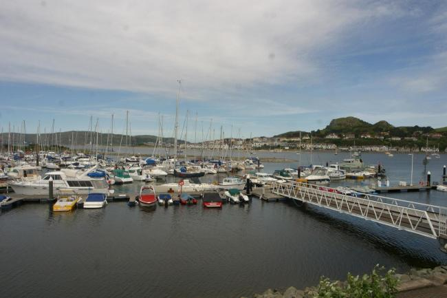 A businessman was found dead on his boat at Conwy Marina, an inquest heard