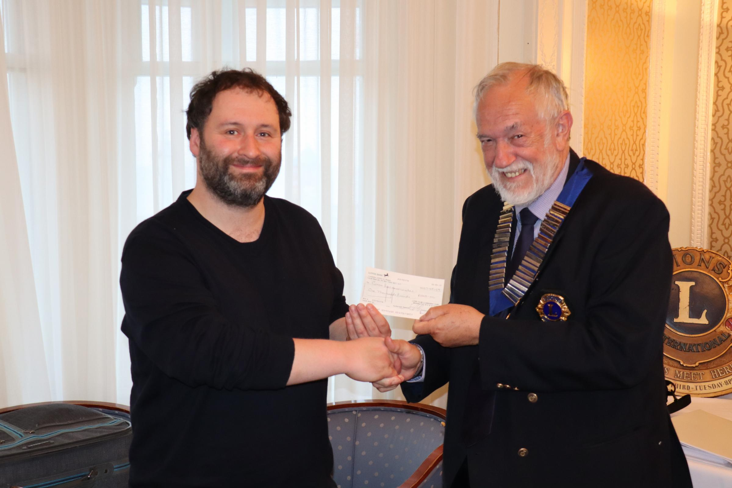 Dr Christopher Staples receives the award from Lions Club President Graham Shimmin